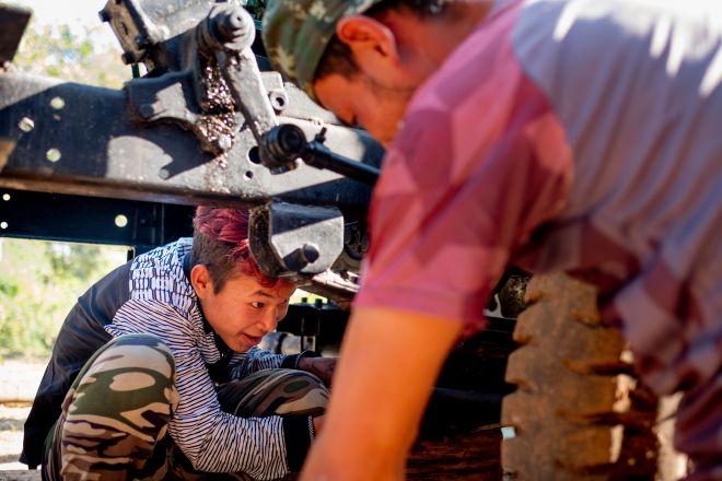 a boy working on motorcycle repair in Myanmar