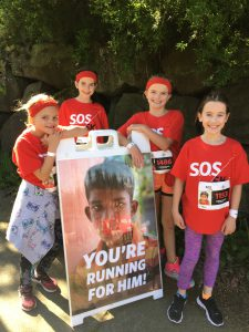 four girls standing around a poster during a run to stop child trafficking