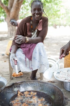 woman frying fish in South Sudan