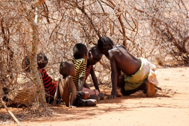 A group of children seek shelter under sparse brush in Northern Kenya's extreme weather.