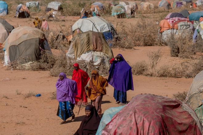 A group of women walking in an IDP camp in Somalia's extreme weather.