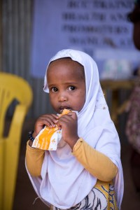 A little girls eats a Nutripacket in Somalia.