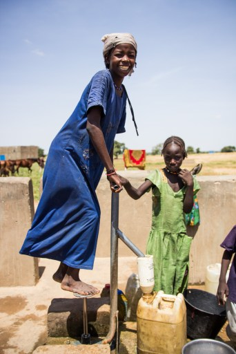 A girl draws water from a pump well.