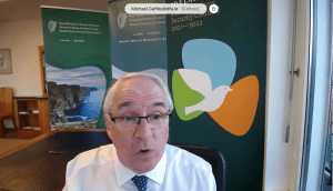 Irish Ambassador Michael Gaffey speaks on a video conference in front of a green background with photos of Ireland.