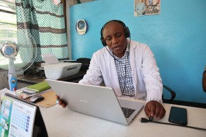 Physician in the Democratic Republic of the Congo speaks to patients remotely, through laptop.