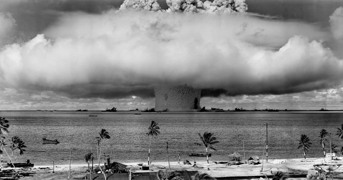 nuclear weapons test in pacific atoll taken from ground level with rising mushroom cloud