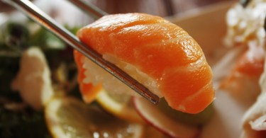 close up of salmon sushi held in chopsticks