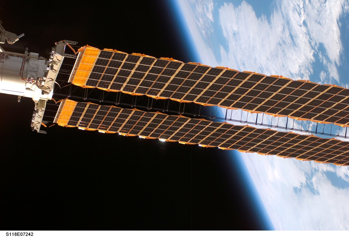 solar panels in space with the earth as background