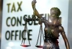 scales of justice with tax written behind it