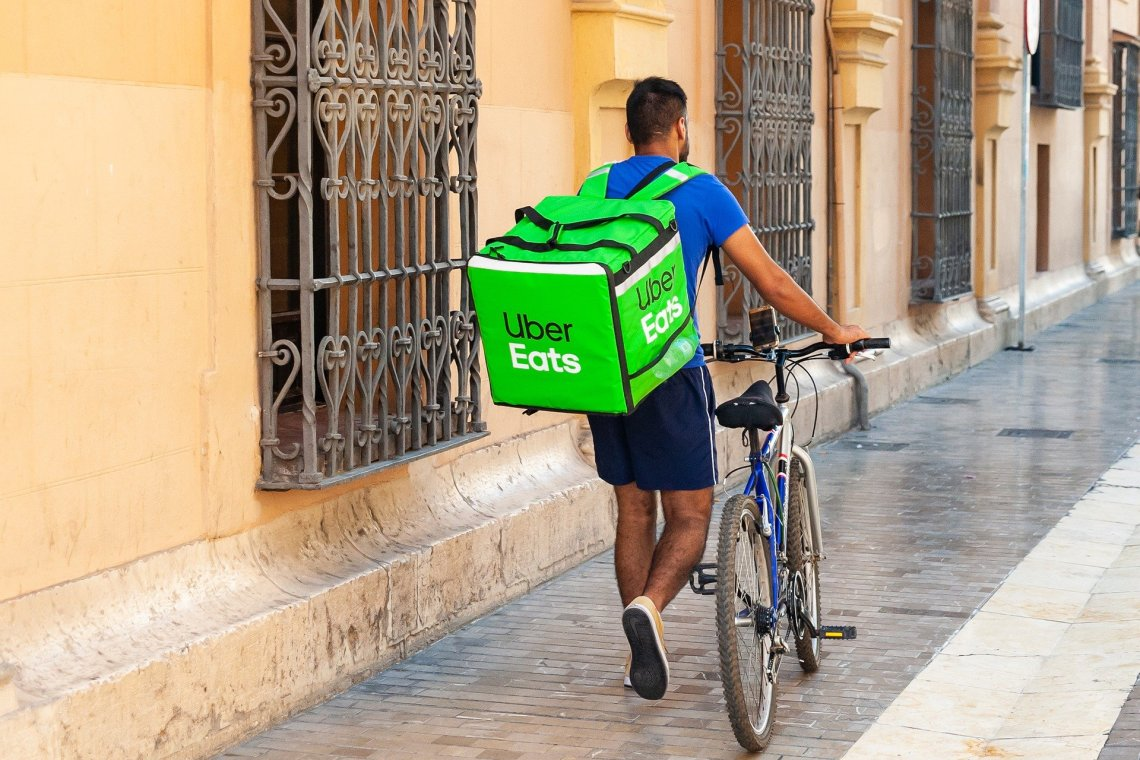 Uber eats delivery rider on pavement with bicycle