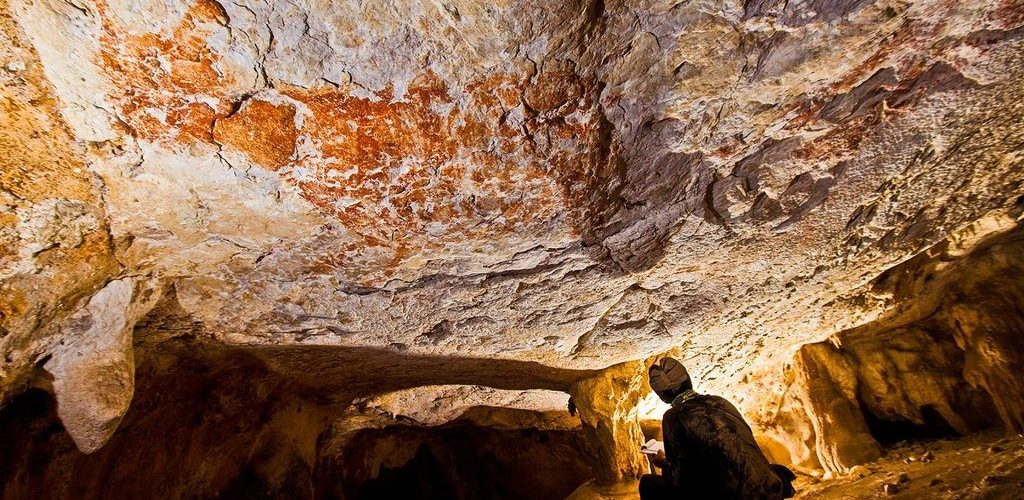 researcher on haunches in Borneo cave looking at ancient rock art