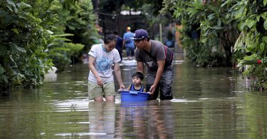 A family walks their son through a flooded neighborhood in a bucket in Tanggerang on the outskirts of Jakarta, Indonesia, Jan. 2, 2020