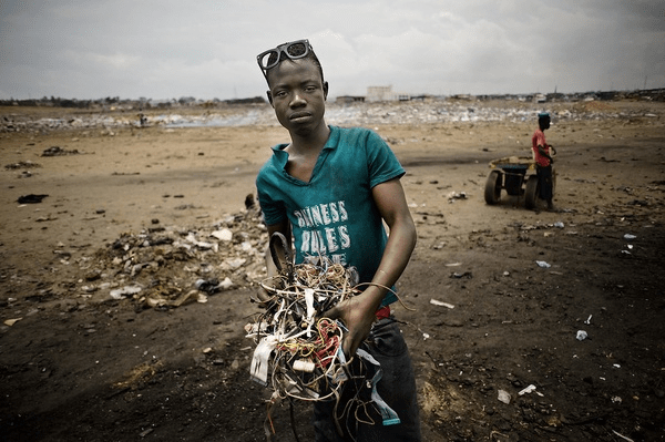 young boy holding e-waste at huge dump in Ghana