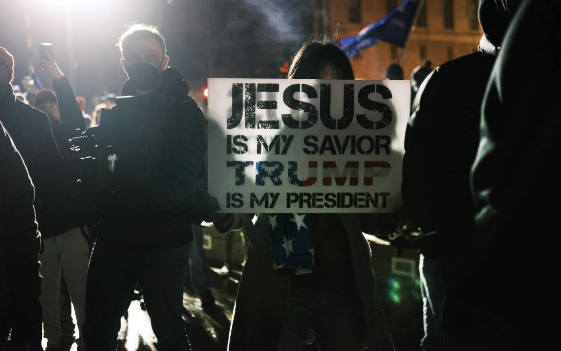 woman protester holding sign saying jesus is my saviour and trump is my president