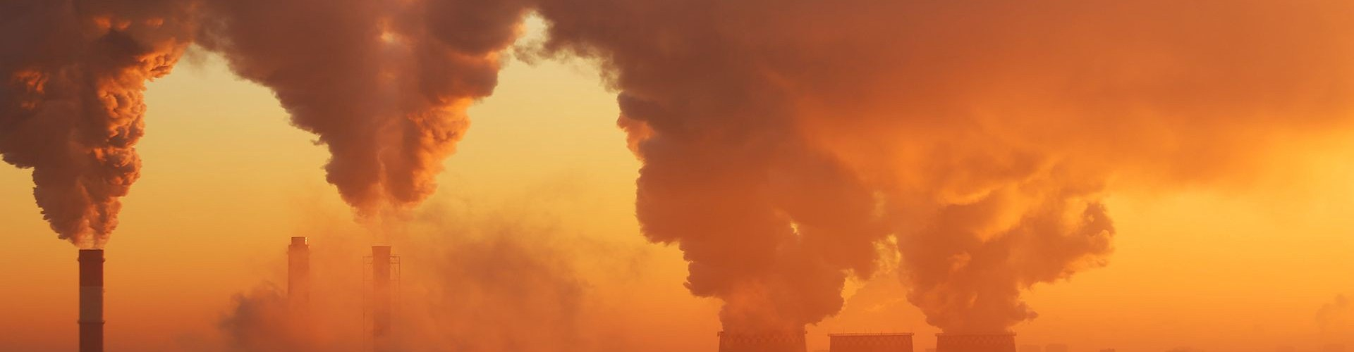 power plant spewing pollution in to sunset sky