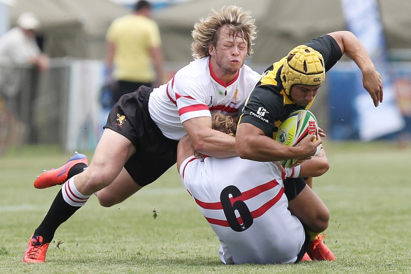 MAN BEING TACKLED DURING GAME OF RUGBY