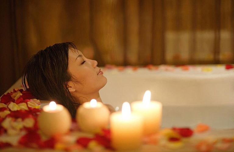 woman in hot bath with candles
