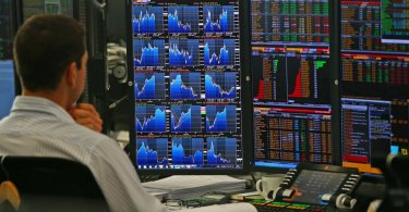 trader sitting in front of multiple screens with financial data