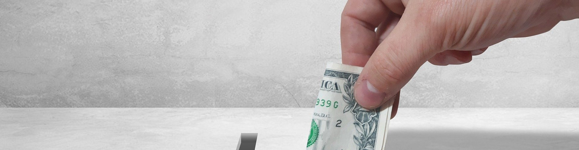 folded dollar being slipped into cross shaped hole