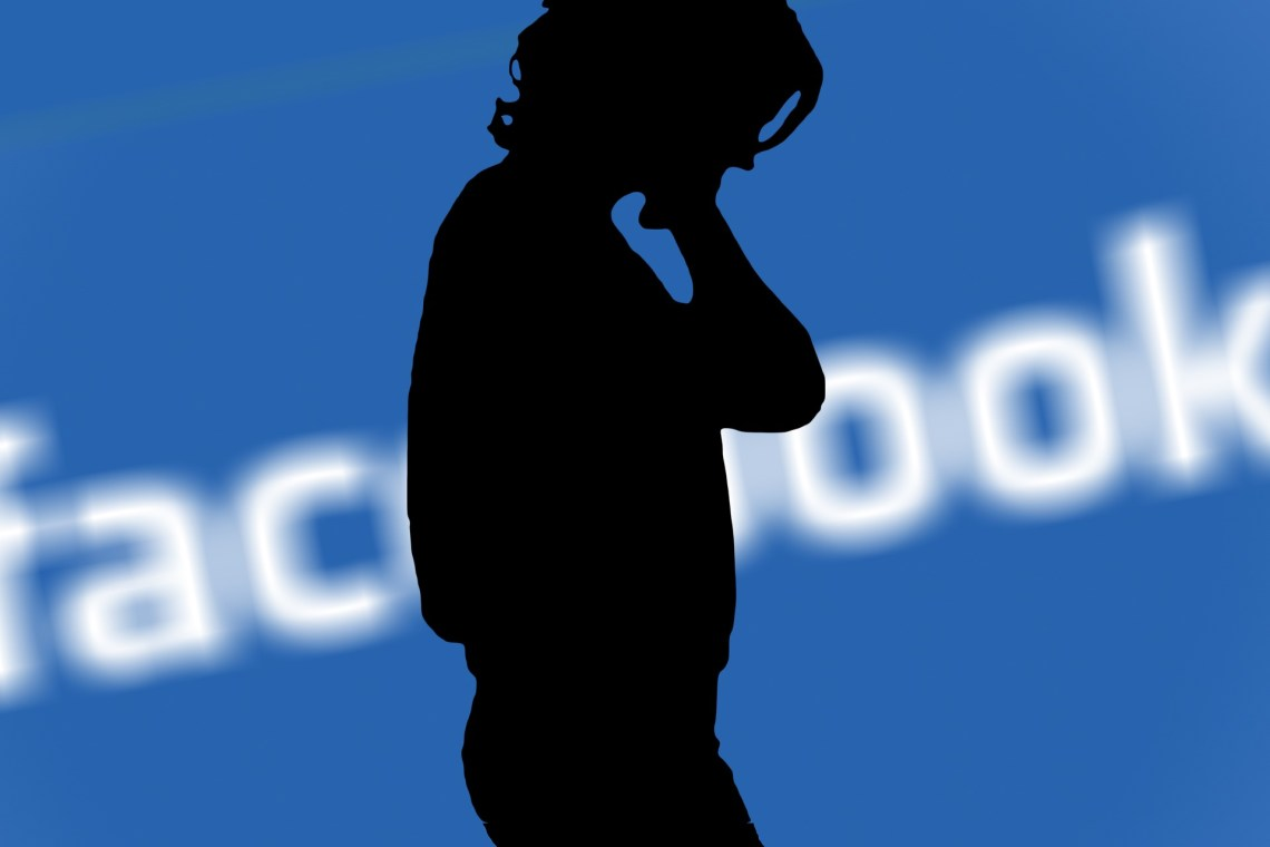 silhouette of woman with facebook background
