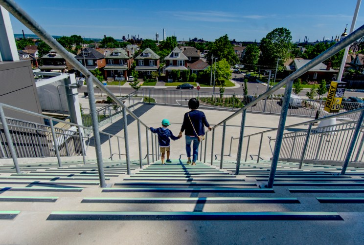 a woman holds her son's hand as they walk down a flight of concrete steps with bold vision strips, holding onto the handrails