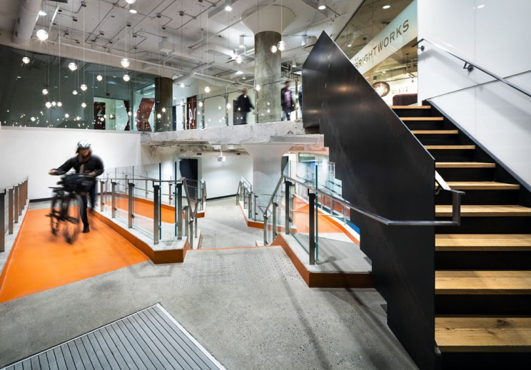 a person walks their bike up the bright orange ramp of the 100 Broadview Avenue lobby, which is predominantly concrete with orange details