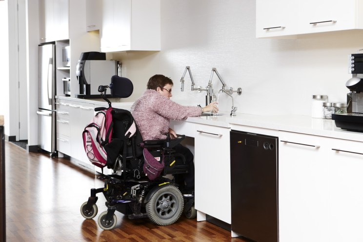 woman in a wheelchair fills a glass with water from the tap