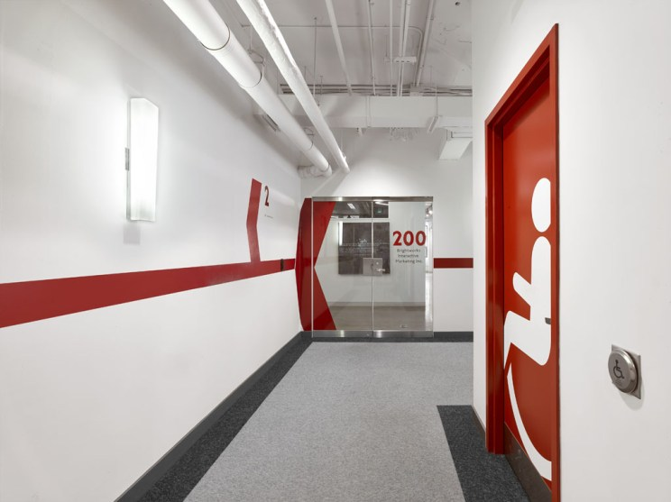 a universal washroom clearly identified by a bright red door decorated with a contrasting white, life-sized universal symbol of access