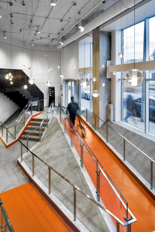 aerial view of a man walking a bicycle up a bright orange ramp in an office building lobby