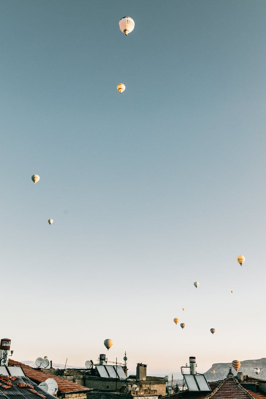 hot air balloons flying over town in daytime