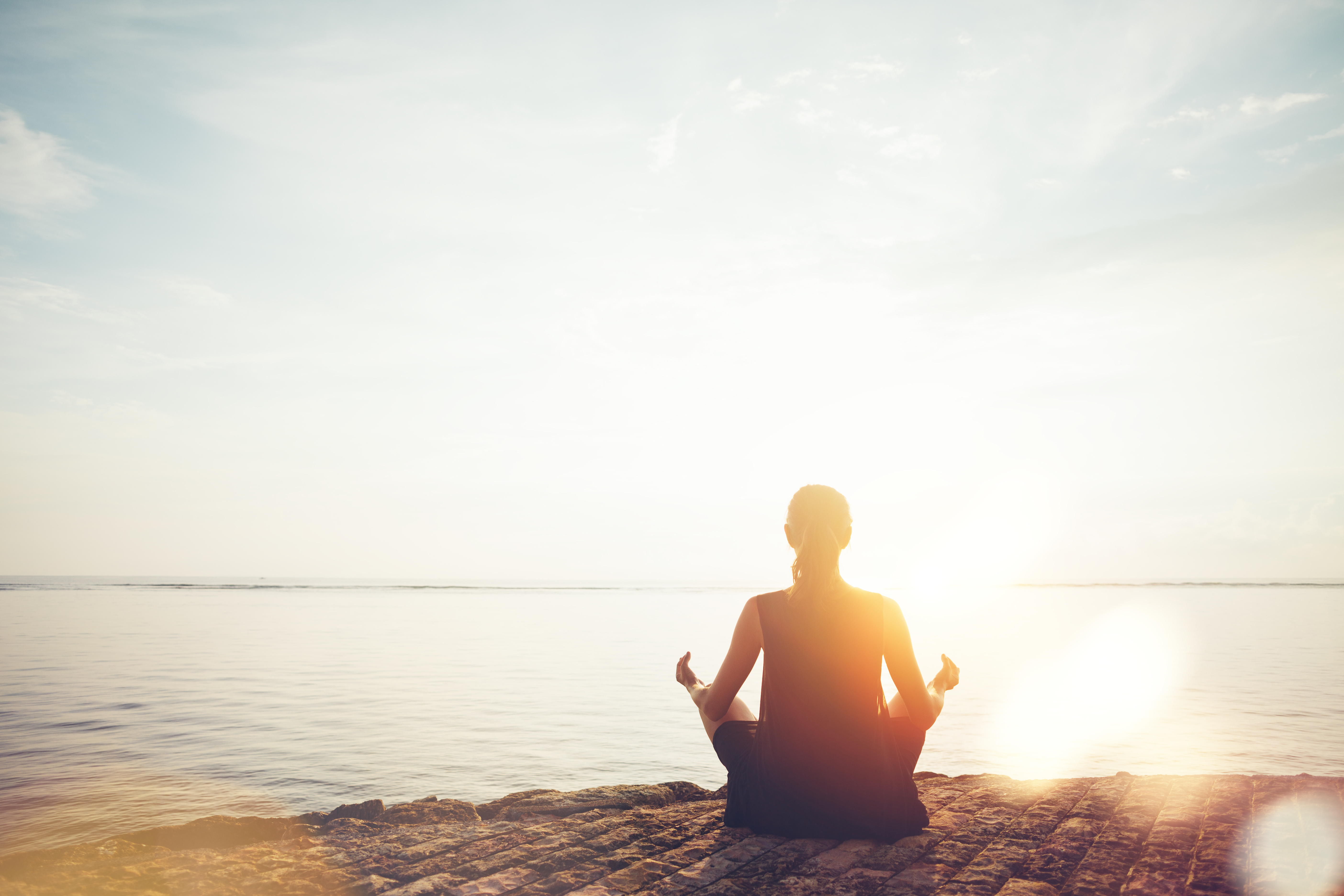 Young woman doing meditation practice on the beach. Intentional sun glare and lens flare effect