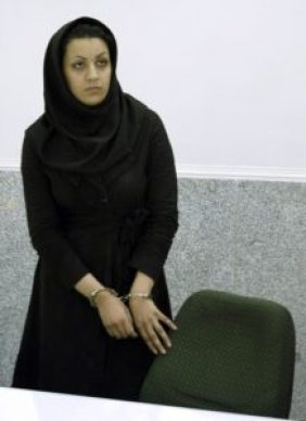 """A picture taken on July 8, 2007 shows Iranian Reyhaneh Jabbari standing handcuffed at police headquarters in Tehran after she was arrested for the murder of a former intelligence official. Jabbari who is awaiting an impending death sentence for slaying of former intelligence official Morteza Abdolali Sarbandi, could be forgiven if """"she tells the truth"""", the victim's son said on April 19, 2014 as a UN human rights monitor claims the crime was done in self-defence against a potential rapist. AFP PHOTO/GOLARA SAJADIAN"""