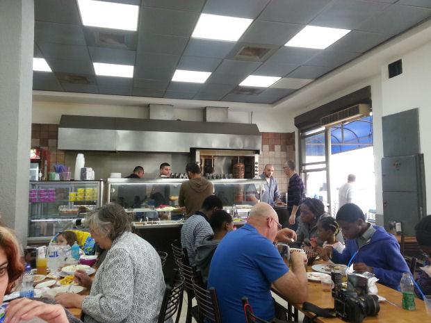 בפנים יש תריסר שולחנות עם אנשים שאוכלים חומוס. עימאד