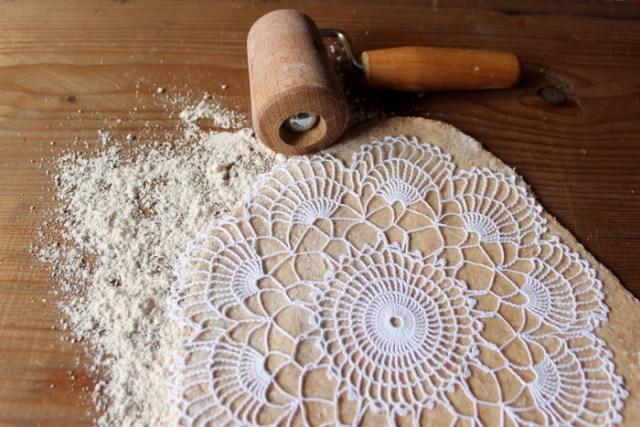 Teig mit aufgelegtem Spitzendeckchen aus dem die Hundekekse hergestellt werden