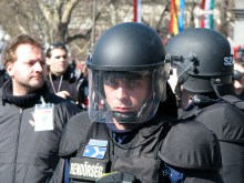 Riot cop protects Budapest Mayor Gábor Demszky from demonstrators during speech (3/15/2008).