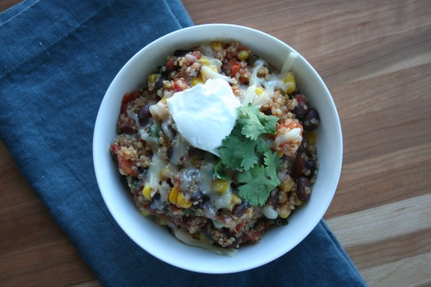 overhead shot of Mexican Quinoa - filled with corn, black beans, fire roasted tomatoes, jalapenos, and topped with melted cheese, cilantro, and Greek yogurt.