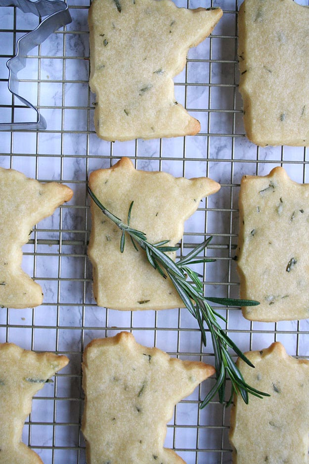 a sprig of rosemary on top of baked rosemary shortbread cookies shaped like Minnesota