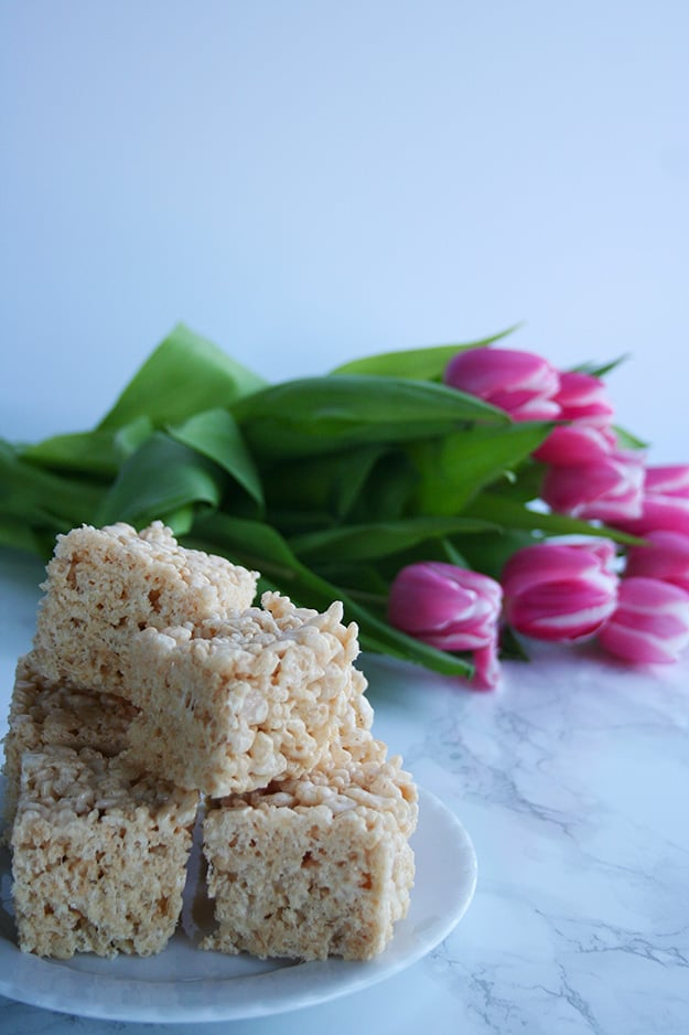 an angled shot of a plate of browned butter Rice Krispie treats with pink tulips blurred in the background