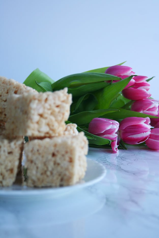 a close up shot of an out of focus plate of browned butter Rice Krispie treats with pink tulips in focus in the background