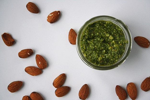 an overhead shot of this ultra green kale almond pesto in a glass jar out of focus on a blank white canvas sprinkled with in focus almonds