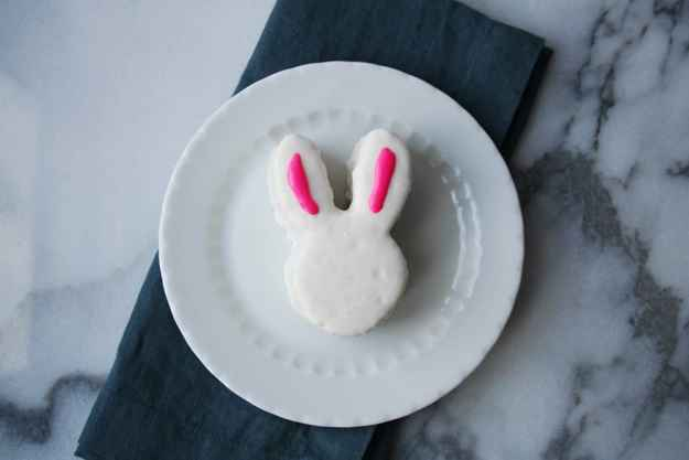 a single mini vanilla pound cake Easter bunny covered in white frosting with pink frosting on the ears - sitting on a white plate with a navy napkin on a marble background