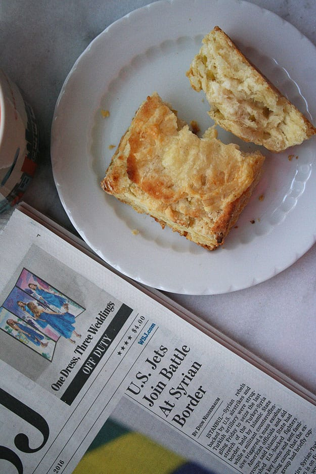 an overhead shot of an apple and white cheddar scone broken open so you can see the flaky texture, plated with a cup of coffee and the newspaper