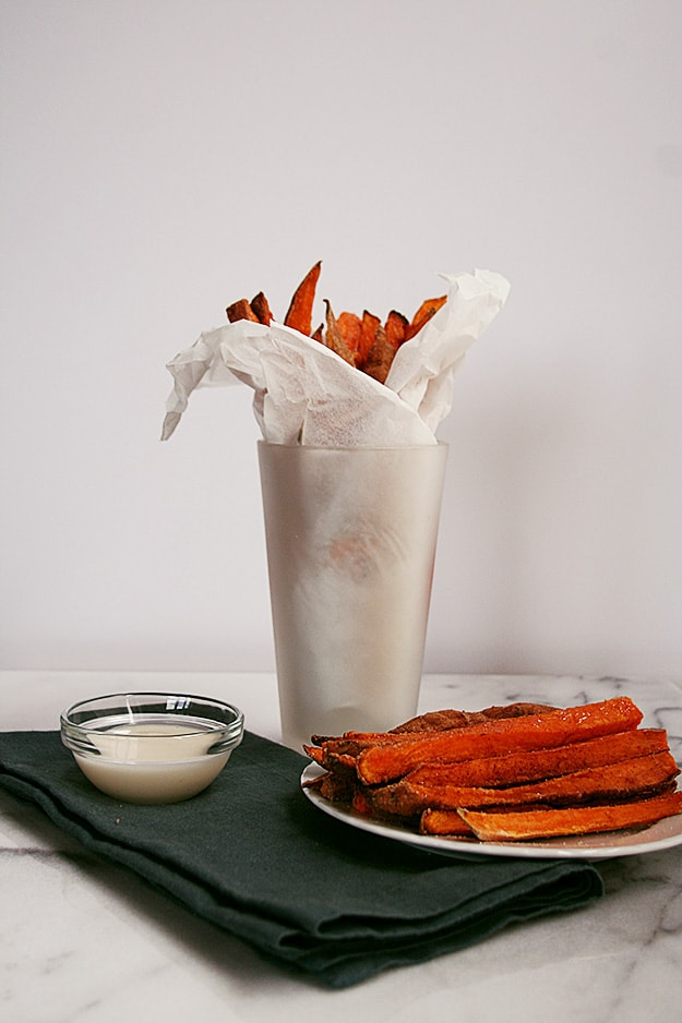 a side shot of a plate of cinnamon sugar sweet potato fries with vanilla glaze dipping sauce in the foreground and a pint glass full of extra fries
