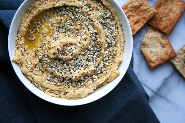 an overhead shot of hummus topped with everything bagel seasoning and a drizzle of olive oil with out of focus pita chips in the background