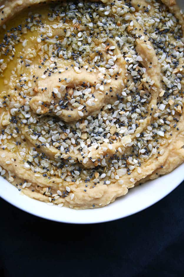 zoomed in on the everything bagel toppings on the bowl of hummus