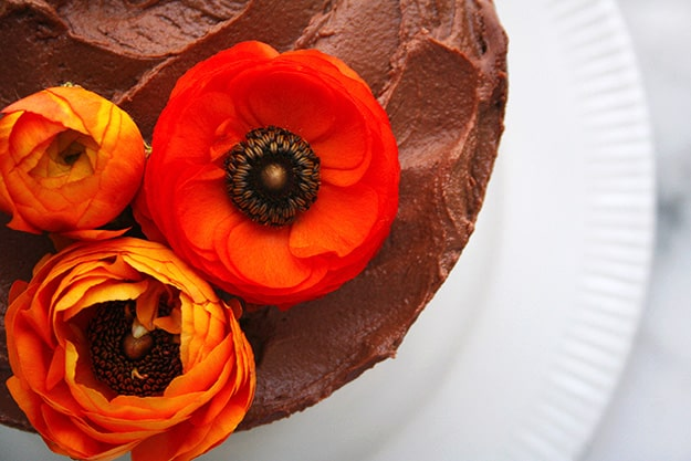 an overhead shot of the orange ranunculus flowers atop a tahini cake with chocolate tahini frosting