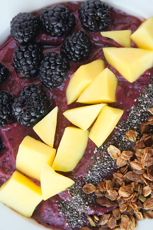 Triple Berry Mango Smoothie Bowl with all the toppings! | hungrybynature.com