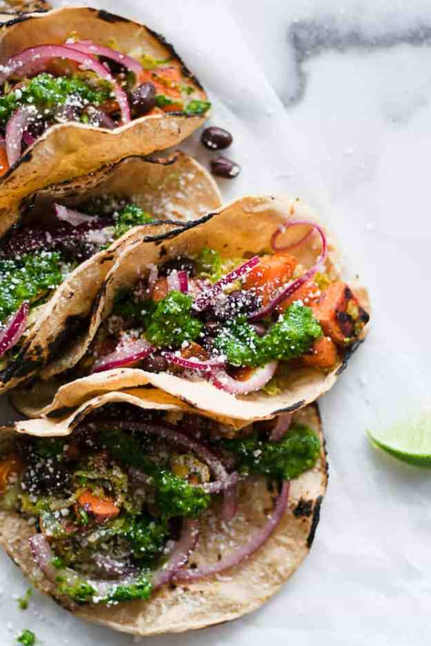 overhead shot of 5 sweet potato and brussels sprout tacos in charred corn torillas sprinkled in cojita cheese, chimichurri sauce, and pickled red onions with lime slices
