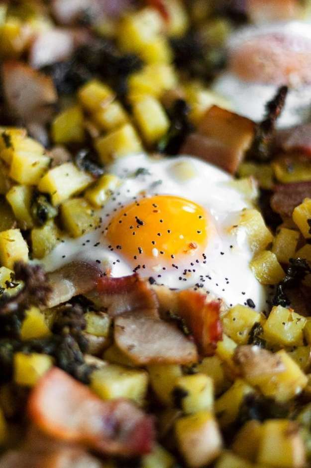 a fried egg sitting on top of a potato bacon and kale hash - sheet pan breakfast bake