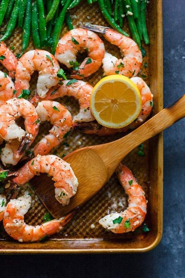 overhead shot of sheet pan shrimp and green beans on a blue backdrop